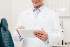 punto di vista parziale di medico sorridente in camice facendo uso della compressa digitale Immagini Stock Libere da Diritti