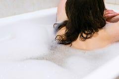 Punto di vista posteriore di bella giovane donna che gode del bagno piacevole con schiuma Fotografia Stock