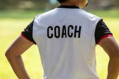 Punto di vista posteriore di calcio maschio o dell'allenatore di football americano in camicia bianca con w fotografia stock
