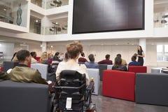 Punto di vista posteriore degli studenti ad una conferenza in un atrio dell'università Immagine Stock