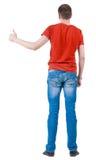Punto di vista posteriore dei giovani in pollice andante della maglietta arancio su. Immagine Stock