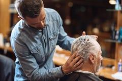 Punto di vista posteriore del barbiere che disegna i capelli del cliente degli anziani immagine stock