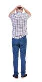 Punto di vista posteriore del giovane arrabbiato in jeans e camicia fotografia stock