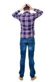 Punto di vista posteriore del giovane arrabbiato in jeans e camicia a quadretti Fotografia Stock
