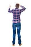 Punto di vista posteriore del giovane arrabbiato in jeans e camicia a quadretti Fotografie Stock
