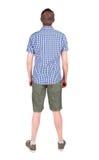 Punto di vista posteriore del giovane in camicia e nello sguardo di shorts Immagini Stock Libere da Diritti