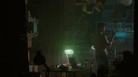 Punto di vista posteriore del giovane che si siede e che lavora a casa alla notte azione Retrovisione dell'uomo che lavora nell'u video d archivio