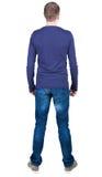 Punto di vista posteriore del giovane nello sguardo dei jeans e della maglietta Immagini Stock