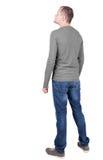 Punto di vista posteriore del giovane nello sguardo dei jeans e della maglietta Fotografie Stock Libere da Diritti