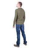 Punto di vista posteriore del giovane nello sguardo dei jeans e della maglietta Fotografia Stock
