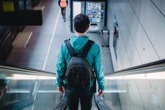 Punto di vista posteriore del giovane viaggiatore in scala mobile della metropolitana fotografia stock