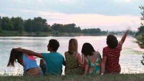 Punto di vista posteriore del gruppo di amici che godono nella natura, nella conversazione e nella risata stock footage