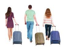 Punto di vista posteriore del gruppo di camminata con la valigia Fotografia Stock