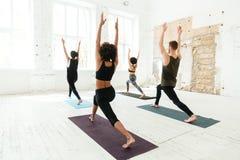 Punto di vista posteriore del gruppo di persone che fanno yoga in palestra Fotografia Stock