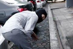 Punto di vista posteriore del ladro mascherato in passamontagna nera che prova a rompersi nell'automobile Concetto criminale di c immagine stock