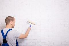 Punto di vista posteriore del pittore del giovane in muro di mattoni w della pittura degli abiti da lavoro Immagine Stock