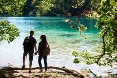 Punto di vista posteriore del ragazzo e della ragazza turistici delle coppie con gli zainhi che stanno sulla sponda del fiume immagine stock libera da diritti