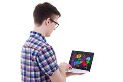 Punto di vista posteriore dell'adolescente che per mezzo del computer portatile con le icone e il appli di media Immagini Stock