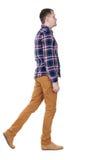 Punto di vista posteriore dell'uomo bello andante in camicia a quadretti Immagini Stock