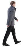 Punto di vista posteriore dell'uomo bello andante di affari in cappotto Fotografia Stock