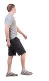Punto di vista posteriore dell'uomo bello di camminata in breve e scarpe da tennis Immagini Stock Libere da Diritti