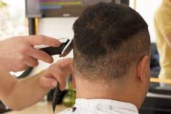 Punto di vista posteriore dell'uomo che ottiene i capelli di scarsità che sistemano al negozio di barbiere con la macchina del ta fotografia stock