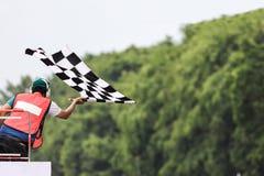 Punto di vista posteriore dell'uomo che tiene la bandiera a quadretti della corsa immagini stock