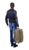 Punto di vista posteriore dell'uomo con cercare verde della valigia Immagini Stock Libere da Diritti