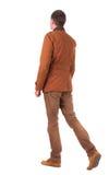 Punto di vista posteriore dell'uomo d'affari di camminata in jeans e rivestimento Immagine Stock Libera da Diritti