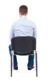 Punto di vista posteriore dell'uomo di affari che si siede sulla sedia Fotografie Stock Libere da Diritti