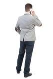 Punto di vista posteriore dell'uomo di affari in vestito che parla sul telefono cellulare Fotografia Stock