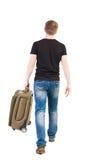 Punto di vista posteriore dell'uomo di camminata con la valigia Fotografia Stock