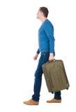 Punto di vista posteriore dell'uomo di camminata in pullover con la valigia Fotografia Stock Libera da Diritti
