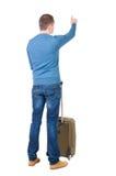 Punto di vista posteriore dell'uomo indicante con la valigia Immagini Stock