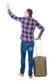 Punto di vista posteriore dell'uomo indicante con la valigia Immagine Stock