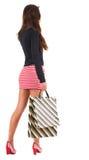Punto di vista posteriore della donna andante in vestito con i sacchetti della spesa. Immagini Stock