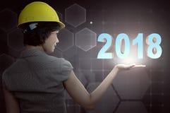 Punto di vista posteriore della donna asiatica dell'ingegnere con la rappresentazione del casco di protezione Immagini Stock