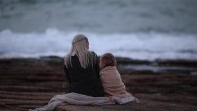 Punto di vista posteriore della donna bionda con la bambina che stringe a sé in plaid su litorale roccioso nel movimento lento cr stock footage