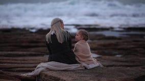 Punto di vista posteriore della donna bionda con la bambina che stringe a sé in plaid su litorale roccioso nel tempo crepuscolare archivi video