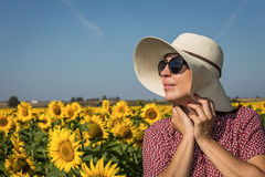 Punto di vista posteriore della donna in cappello che esamina girasole immagine stock libera da diritti