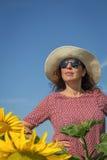 Punto di vista posteriore della donna in cappello che esamina girasole fotografie stock