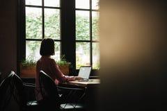 Punto di vista posteriore della donna castana che si siede dalla tavola vicino alla finestra Fotografia Stock Libera da Diritti
