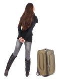 Punto di vista posteriore della donna castana di viaggio in jeans con il gabinetto della valigia Fotografia Stock