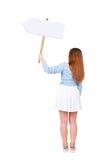Punto di vista posteriore della donna che mostra un bordo del segno Immagine Stock