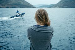 Punto di vista posteriore della donna che pensa da solo e che guarda il mare con Immagine Stock Libera da Diritti