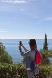 Punto di vista posteriore della donna che prende foto di waterscape Fotografie Stock Libere da Diritti