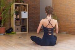 Punto di vista posteriore della donna che si siede nella posa del loto di yoga che si rilassa e che medita nel salone immagini stock