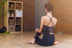 Punto di vista posteriore della donna che si siede nella posa del loto di yoga che si rilassa e che medita nel salone immagine stock libera da diritti
