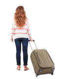 Punto di vista posteriore della donna di camminata con la valigia. Fotografia Stock