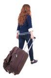 Punto di vista posteriore della donna di camminata con la valigia Fotografia Stock